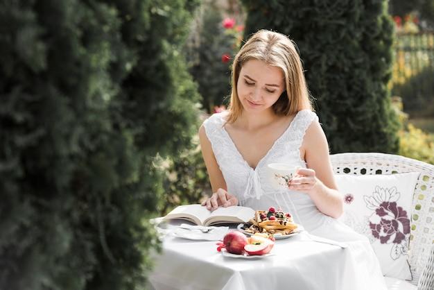 屋外のテーブルで朝食をとりながら本を読む若い女性