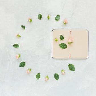 Роза и листья украшения с открытым дневником на бетонном фоне