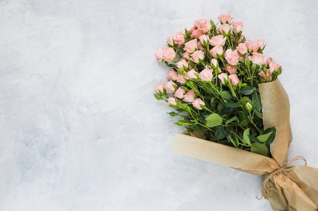 Букет из розовых роз, завернутый в оберточную бумагу с ниткой на бетонной стене