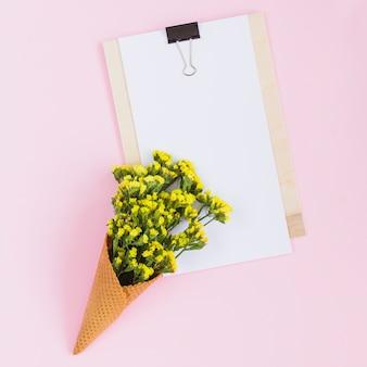 ピンクの背景にクリップボードの上に黄色の花とワッフル