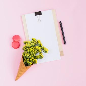 マカロン;クリップボード;ピンクの背景にアイスクリームコーンのペンと黄色の花