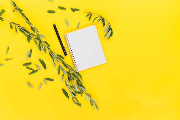 黄色の背景にペンとスパイラルの空白のメモ帳と緑の葉