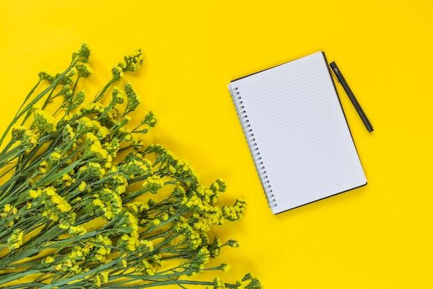 Спиральный блокнот и ручка рядом с букетом свежих цветов на желтом фоне