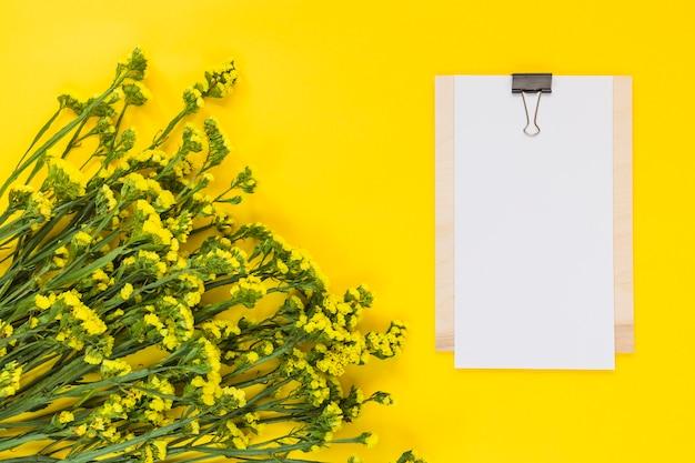 Чистый лист бумаги в буфер обмена с букетом цветов на желтом фоне