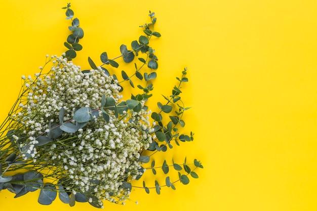 Букет из цветочков и листьев на желтом фоне