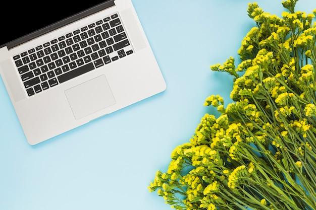 青い背景に開いたノートパソコンと黄色の花