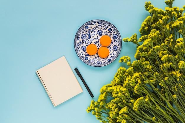 セラミックプレート上のマカロン;スパイラルメモ帳。ペン、青い背景の黄色の花の束
