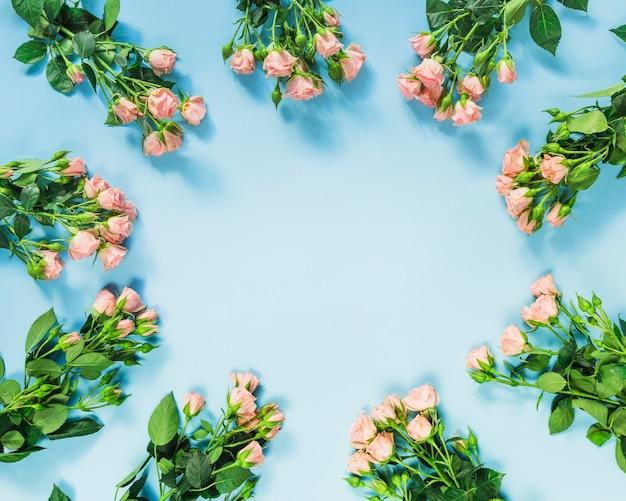 青い背景にバラの束で作られた円形のフレーム