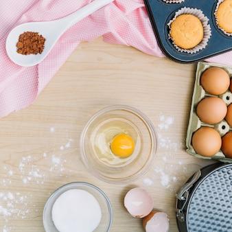 食材と木製の机の上のケーキを作るためのツール