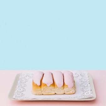 青い背景に対してトレイ上のドイリーにアイシングで覆われたアイスパンや指