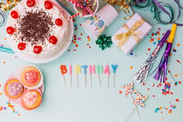 パーティーのアクセサリーと青い背景にケーキの単語誕生日の蝋燭