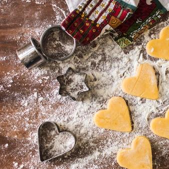 タオルやカッターの近くの生のクッキー