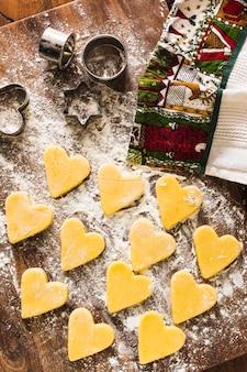 Печенье в форме сердца рядом с полотенцем и резаками