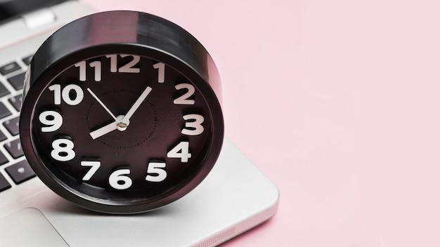ピンクの背景のラップトップ上の目覚まし時計