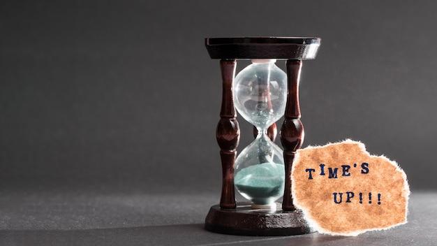 Время вверх текст на рваной бумаге возле песочных часов на сером фоне