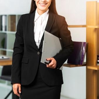 Улыбается бизнесвумен, стоя в офисе, проведение буфера обмена