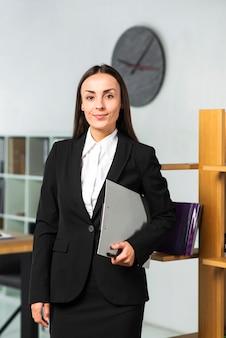 Уверенно улыбается бизнесвумен, держа в руке буфера обмена и ручка