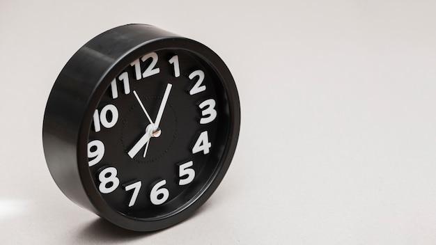 灰色の背景に対して円形の黒い目覚まし時計