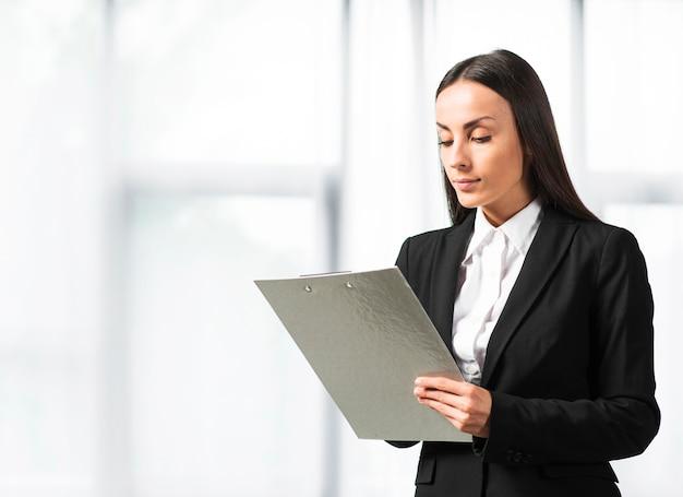 窓の近くに立っているクリップボードに書く実業家のクローズアップ