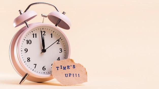 ベージュ色の背景に対して目覚まし時計の近く引き裂かれた紙の上のテキストをタイムズします。