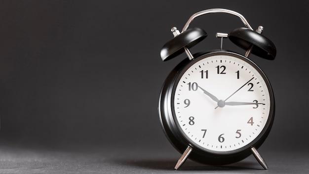 黒の背景にレトロな黒の目覚まし時計