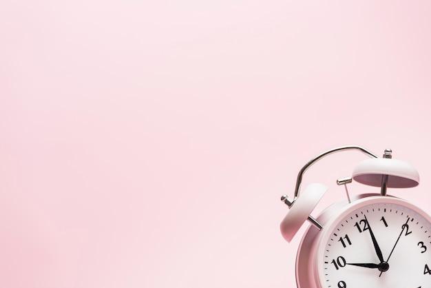 ピンクの背景の隅にある小さな目覚まし時計