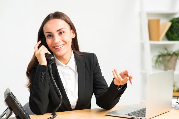 机の上のノートパソコンと電話で話しながら身振りで示す若い女性の笑みを浮かべてください。