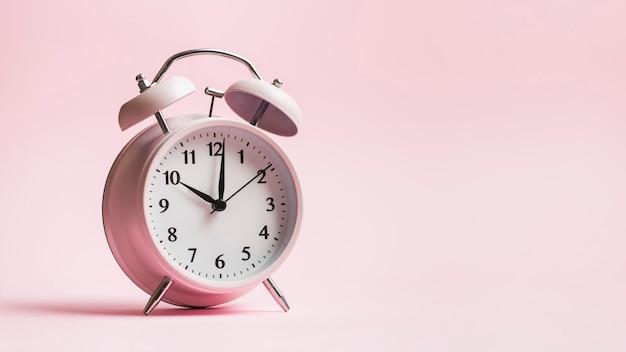 ピンクの背景にビンテージの目覚まし時計