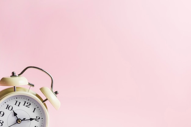 ピンクの背景の隅にレトロな目覚まし時計
