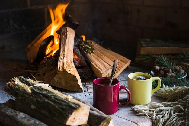 暖炉の近くのログと飲み物