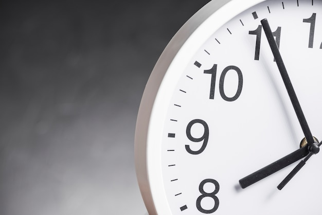 灰色の背景に対して時計の文字盤のクローズアップ