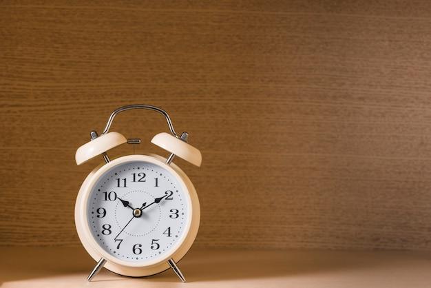 木製の織り目加工の背景に対してビンテージの目覚まし時計