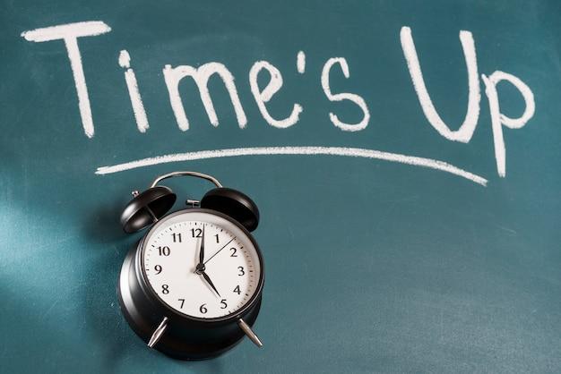 テキストまでの時間と緑の黒板にビンテージの目覚まし時計
