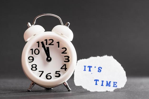 黒の背景に白い目覚まし時計の近くの引き裂かれた紙の上のその時間青いテキスト