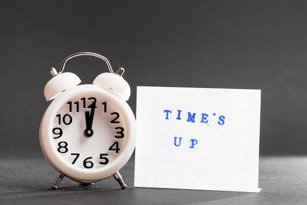 黒い背景に白い目覚まし時計の近くの接着メモに青いテキストをタイムズします。