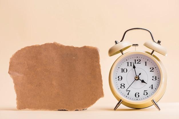 色付きの背景に対して目覚まし時計の近くの空白の茶色の破れた紙