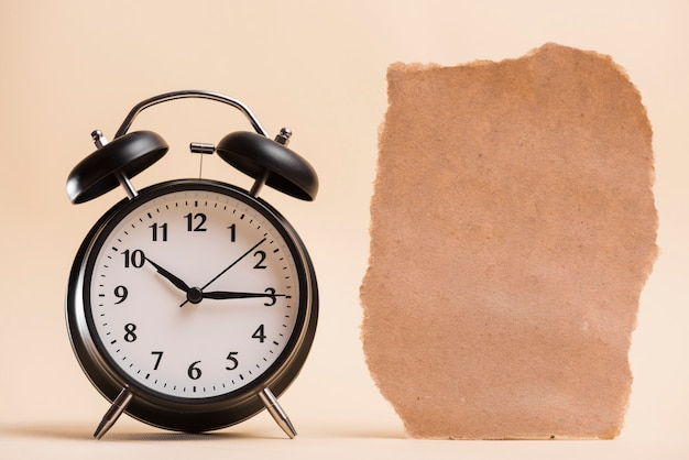 色付きの背景に対して黒の目覚まし時計の近くの空白の茶色の破れた紙