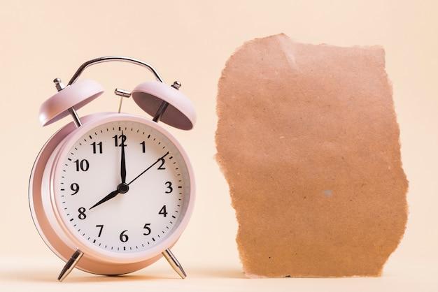 ベージュ色の背景に引き裂かれた紙の破片の近くのピンクの目覚まし時計