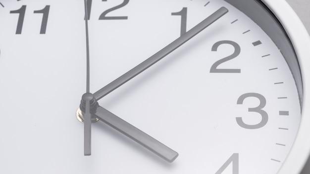 白い時計の文字盤に手のクローズアップ