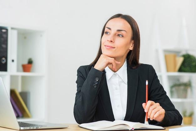 Рассматриваемая молодая коммерсантка держа карандаш в руке на дневнике