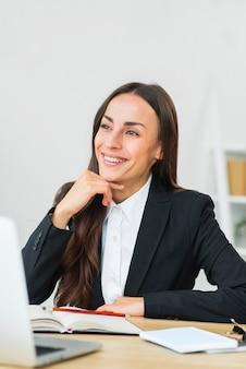 机のそばに座って笑顔空想若い実業家