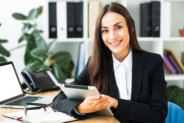 Портрет молодой коммерсантки сидя на столе держа цифровую таблетку в ее руке