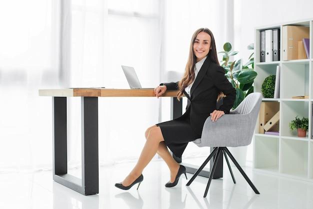 彼女の近代的なオフィスの机に座って自信を持って笑顔若い実業家