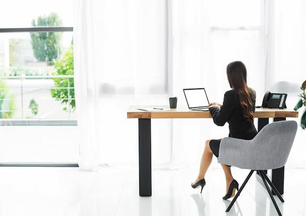 近代的なオフィスのインテリアにラップトップを使用して実業家の背面図