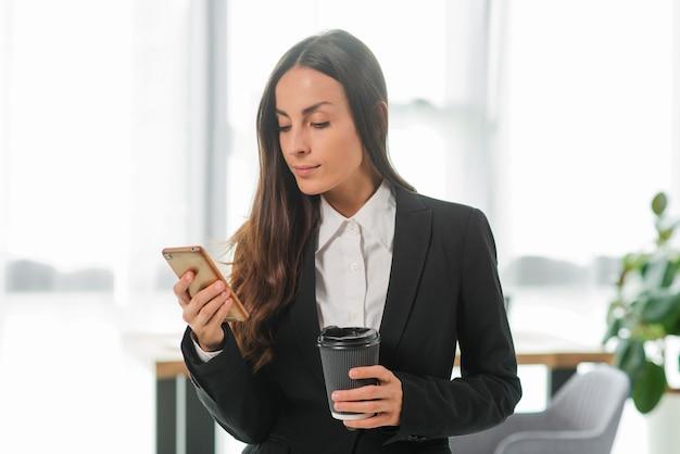 使い捨てのコーヒーカップを保持している携帯電話を見て実業家