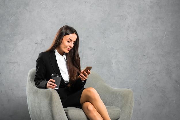 灰色の背景に対して携帯電話を使用して肘掛け椅子に座っている女性実業家