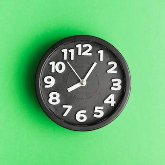 緑の背景に黒の目覚まし時計