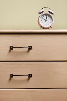木製の閉じた引き出しの上の目覚まし時計