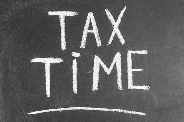 チョークで黒いバックボードに書かれた納税時間