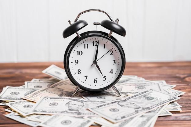 木製の織り目加工の背景の上のスプレッド通貨ノートの目覚まし時計